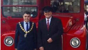 Mayor Adam Zair with the driver of red vintage bus
